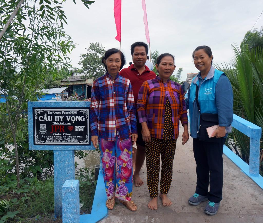 '희망의 다리' 현판과 주민들(왼쪽에서 두번째 Thuy씨)